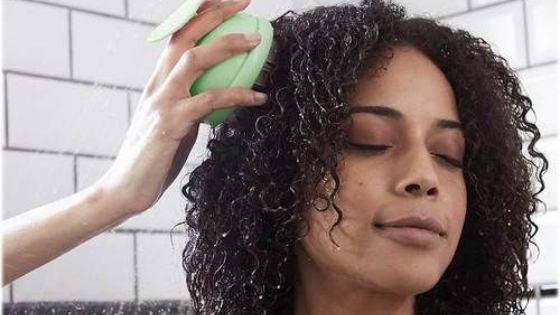 How to love your natural hair on wash day. Lady using scalp massager brush.
